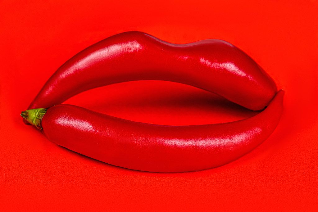 Lips made from hot chili peppers on a red background