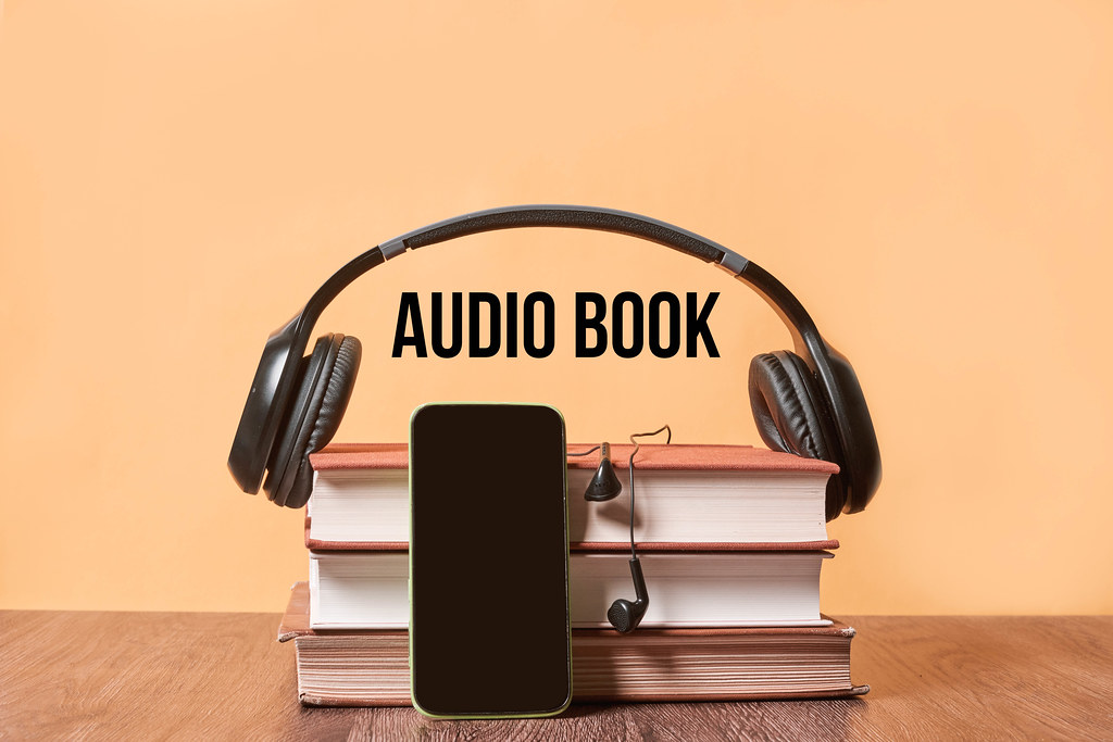Listening audiobook - Stack of books, mobile phone with empty screen and headphones