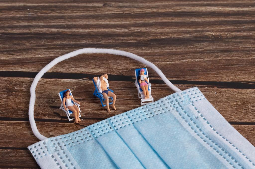 Little miniature people sunbathing on a beach