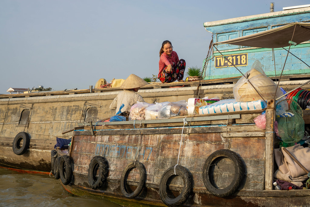 Local Woman pointing at Goods on a Boat Shop from a larger Ship at Cai Rang Floating Market in Can Tho, Vietnam