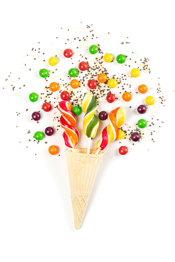 Lollipops in waffle cone and multicolored chocolate candies on white background