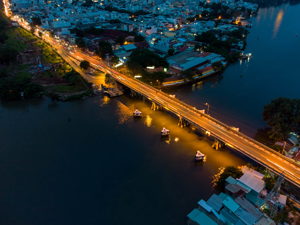 Long Exposure Drone Photo of a Small Bridge over Saigon River connecting District 7 and District 8 at Night in Ho Chi Minh City, Vietnam