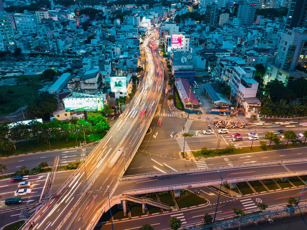 Long Exposure Drone Photo with Traffic Light Streaks on a Bridge over a Highway with many Buildings in Ho Chi Minh City, Vietnam