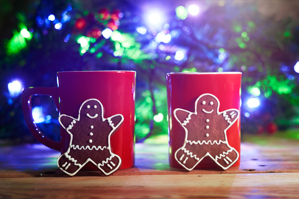 Love in Christmas. Two cups of coffee and festive cookies over the Christmas tree background