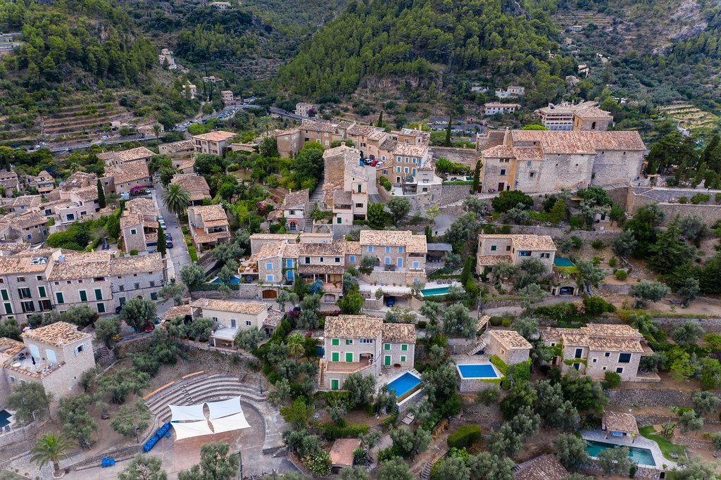 Luftaufnahme der Häuser von Deià mit Pools mitten im Grünen. Künstlerdorf an der Westküste Mallorcas