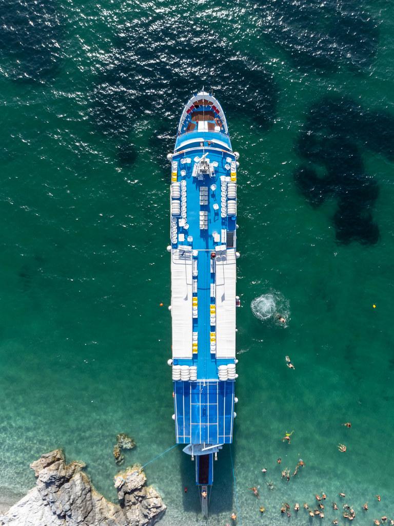 Luftaufnahme des Kreuzfahrtschiffs Elisabet umgeben von Touristen in den Gewässern des Strandes Kastani