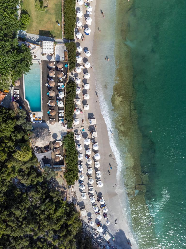 Luftaufnahme des Limnonari-Strandes mit weißen sechseckigen und Stroh-Sonnenschirmen und Schwimmbad