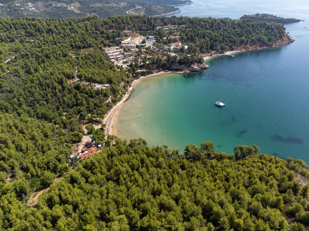 Luftaufnahme des Strandes und der Bucht von Chrisi Milia mit einem Katamaran im türkisfarbenen Meer