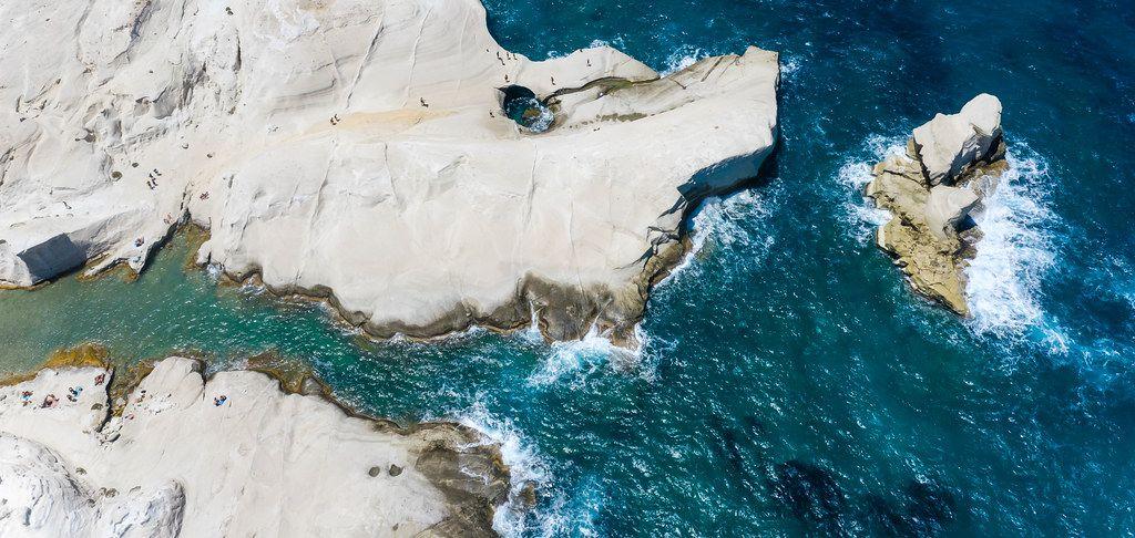 Luftaufnahme: die weißen Klippen von Sarakiniko auf Milos, mit einem von den Wellen geformten Loch