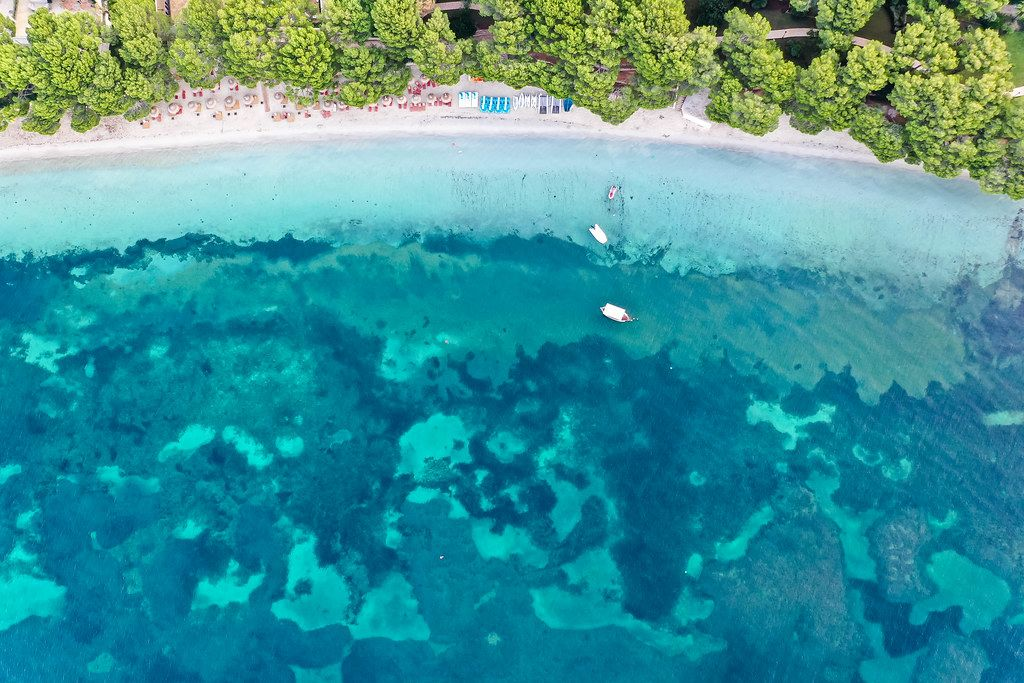 Luftaufnahme: Platja de Formentor auf Mallorca. Strand mit Kiefern, türkisem Wasser und drei Booten