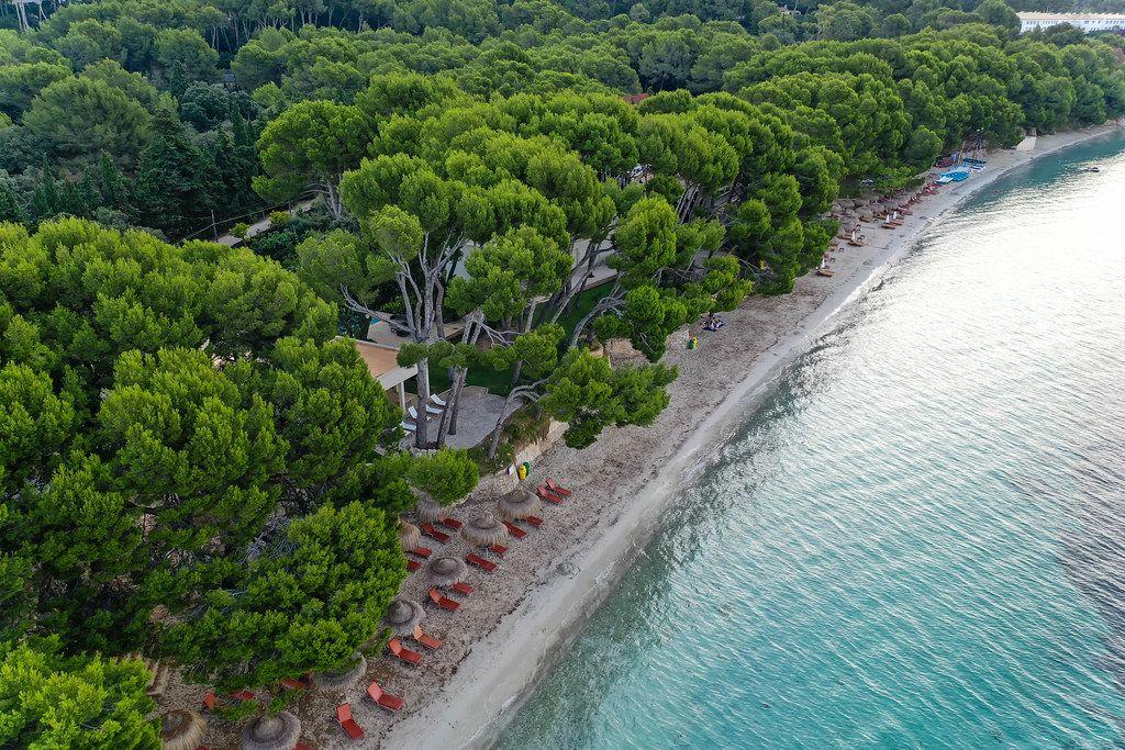 Luftaufnahme: Playa de Formentor auf Mallorca mit braunen Sonnenliegen und Strohsonnenschirmen