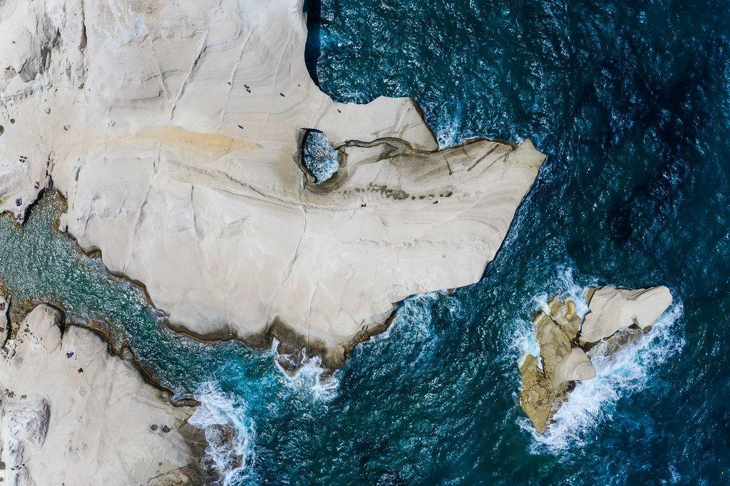 Luftaufnahme von der Küste auf Milos mit schmaler Bucht und großem Loch in der weißen Felswand