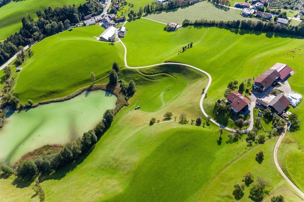 Luftaufnahme von grüner Landschaft mit Bäumen, Häusern und dem Frauensee mit hellgrünem Wasser