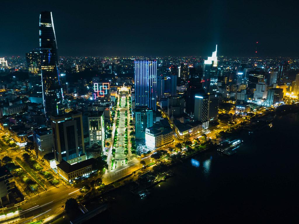 Luftaufnahme von Nguyen Hue Fußgängerzone neben dem Bitexco Financial Tower im Distrikt 1 bei Nacht in Ho Chi Minh Stadt, Vietnam