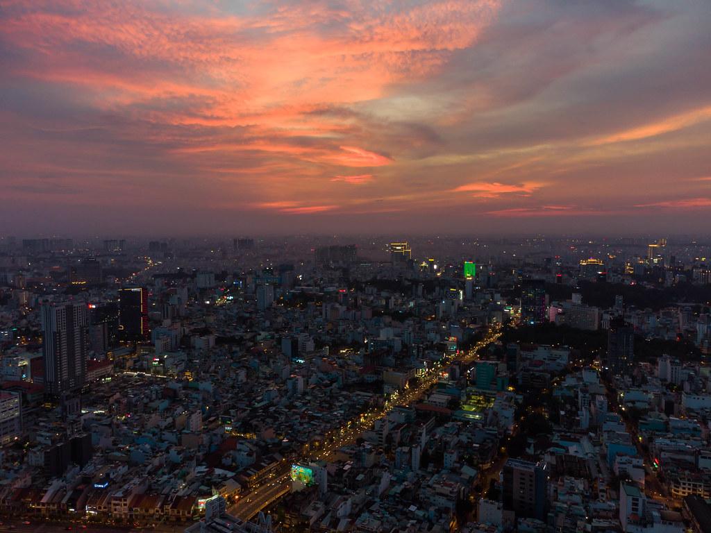 Luftaufnahme von vielen Gebäuden und beleuchteten Straßen bei Sonnenuntergang mit farbenfrohem Himmel in Ho Chi Minh Stadt, Vietnam