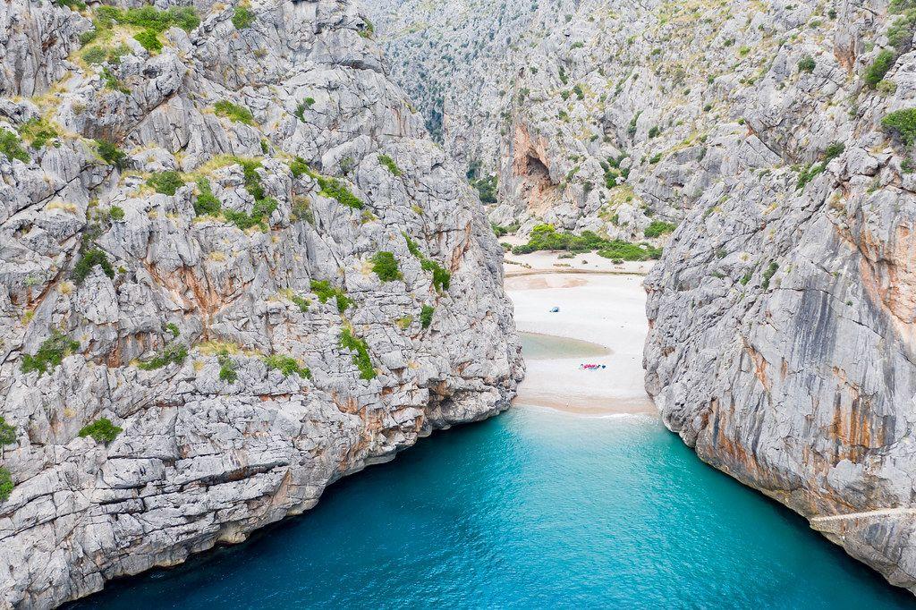 Luftbild: Der versteckte Strand von Sa Calobra, Mallorca. Türkises Wasser zwischen steilen Klippen