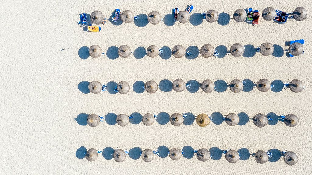 Luftbild: Fünf Reihen Sonnenschirmen werfen ihren Schatten auf den Sand. Cala Mesquida, Mallorca