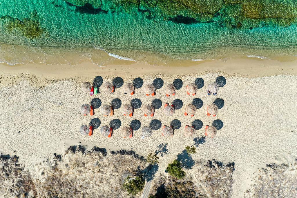 Luftbild: Geometrie am Strand auf Naxos. Drei Reihen von Strandschirmen aus Stroh, Dünen und Meer