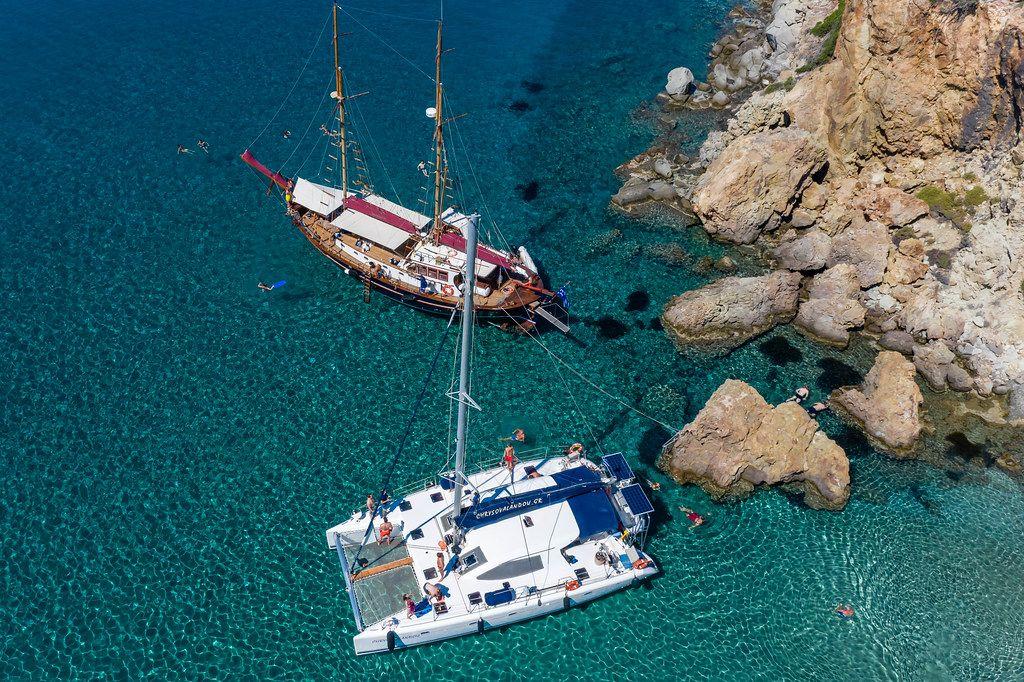 Luftbild: Katamaran und Segelboot. Die Küste von Milos (Griechenland) auf einer Bootstour entdecken