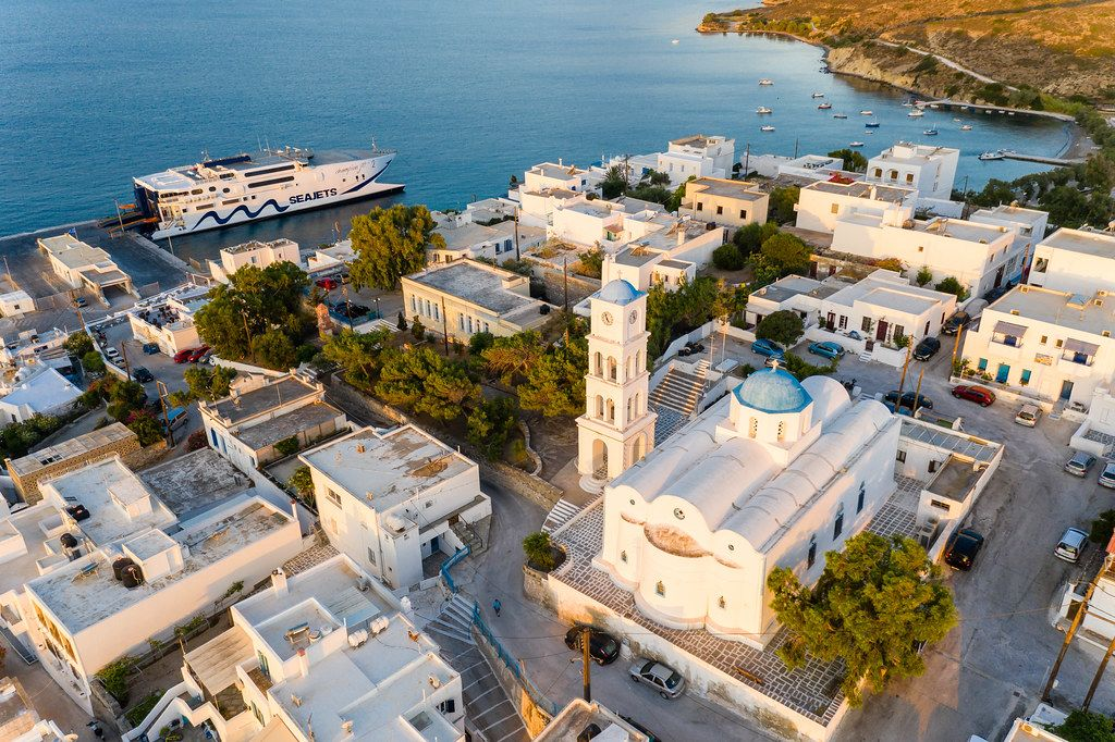 Luftbild von Adamantas auf Milos mit weißer Kirche und Glockenturm mit den typischen blauen Kuppeln