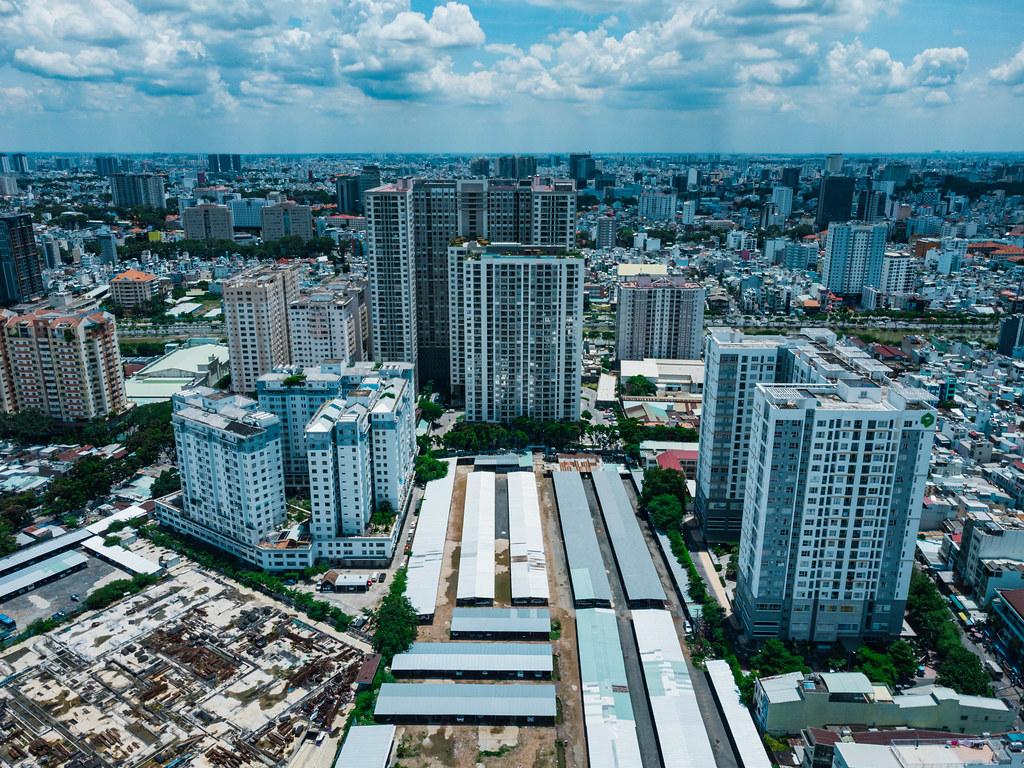 Luftbild von Apartmentgebäuden, einer Baustelle und einem großen Parkplatz in Distrikt 4 in Ho Chi Minh Stadt, Vietnam