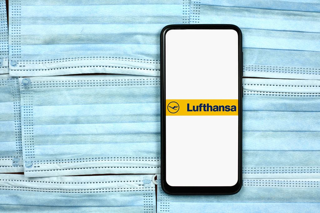 Lufthansa logo on cell phone display over face masks. Impact of coronavirus on global business