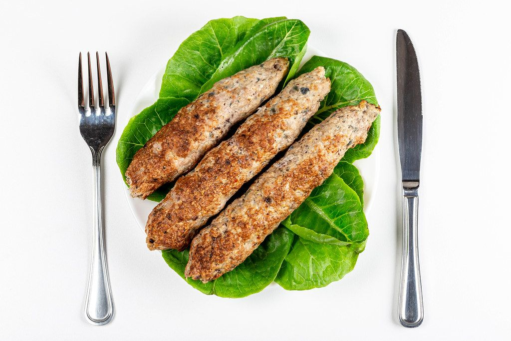 Lula kebab with romaine lettuce on a white plate, top view