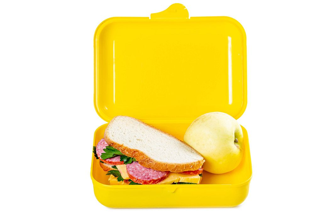 Lunch box with sandwich and apple on white background
