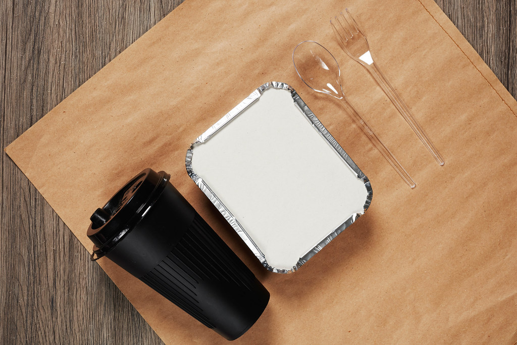 Lunchbox with food, coffee cup, plastic spoon and fork on crafty paper package