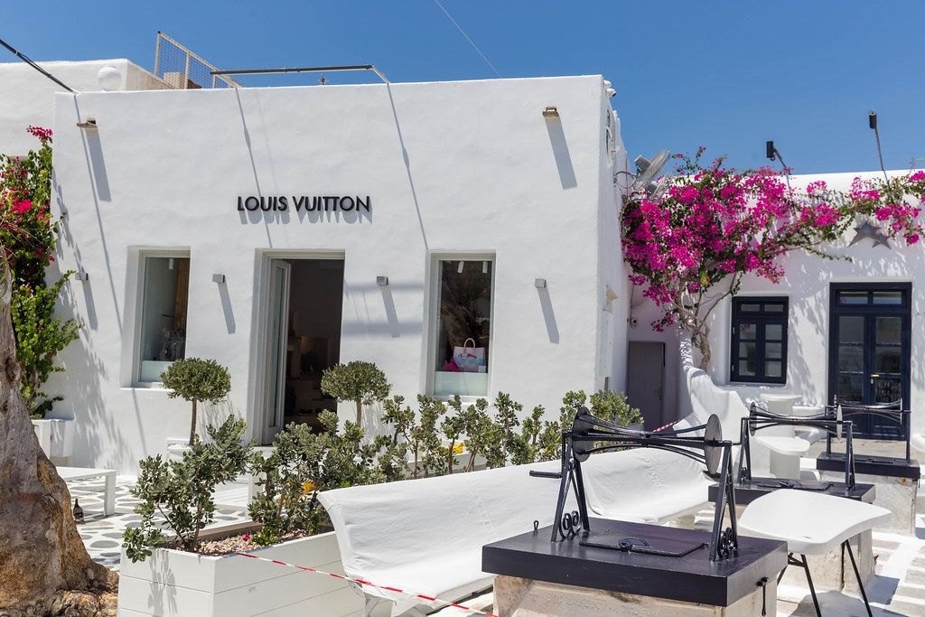 Luxury shopping in Mykonos: Louis Vuitton shop in a white building with plants and open-air terrace