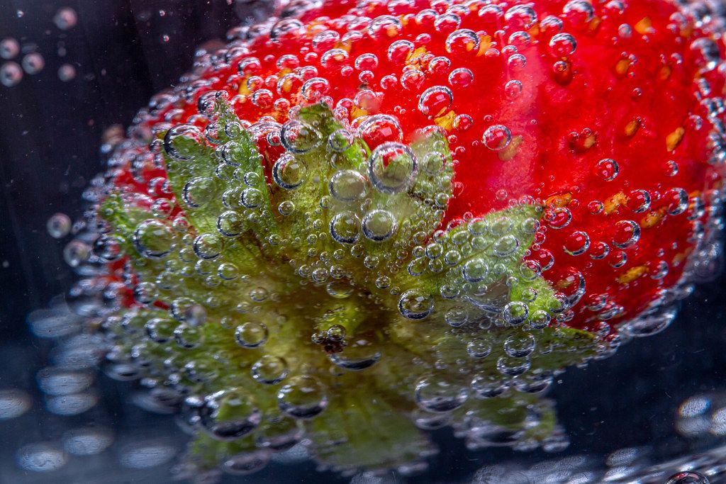 Macro photography of strawberry berries covered with air bubbles
