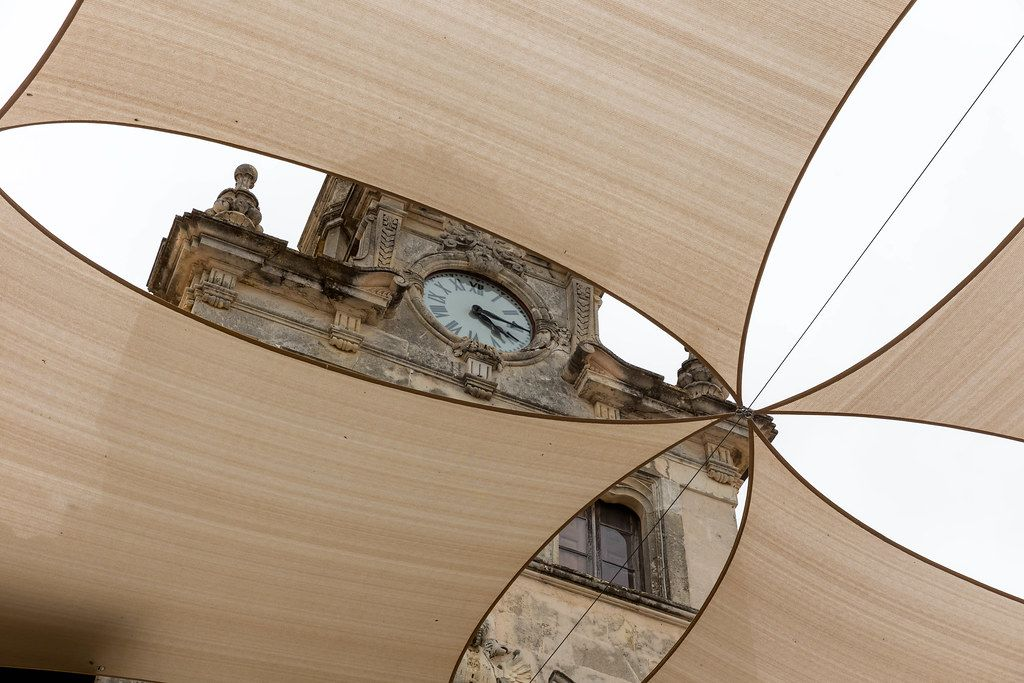 Majorca: the clock on the facade of the Alcudía town hall, framed by large square shade sails