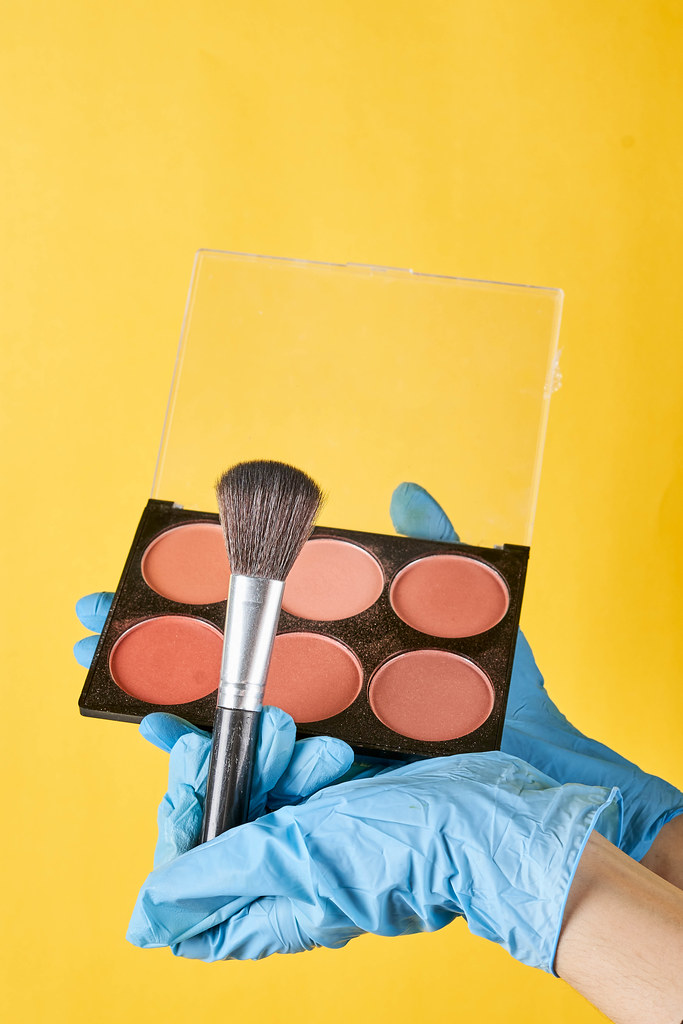 Make-up artist in protective medical gloves holding brush and blush