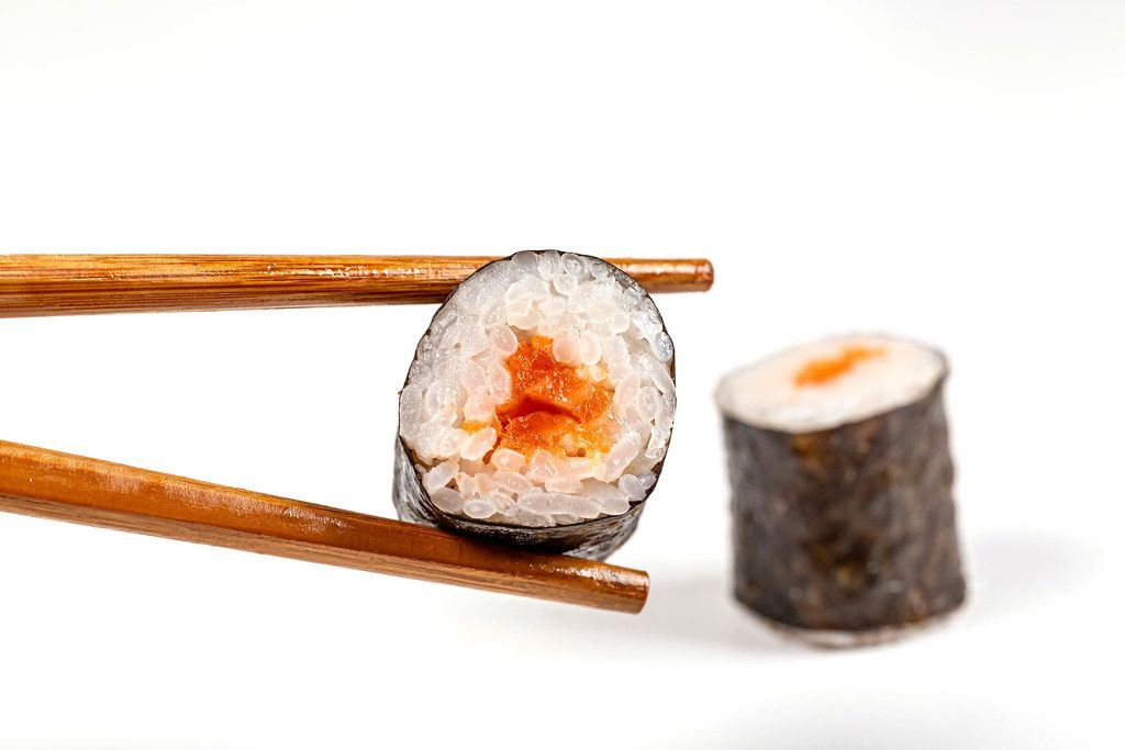 Maki roll with salmon and chopsticks on a white background