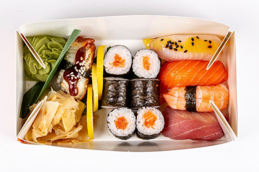 Maki rolls and nigiri in a cardboard box, top view