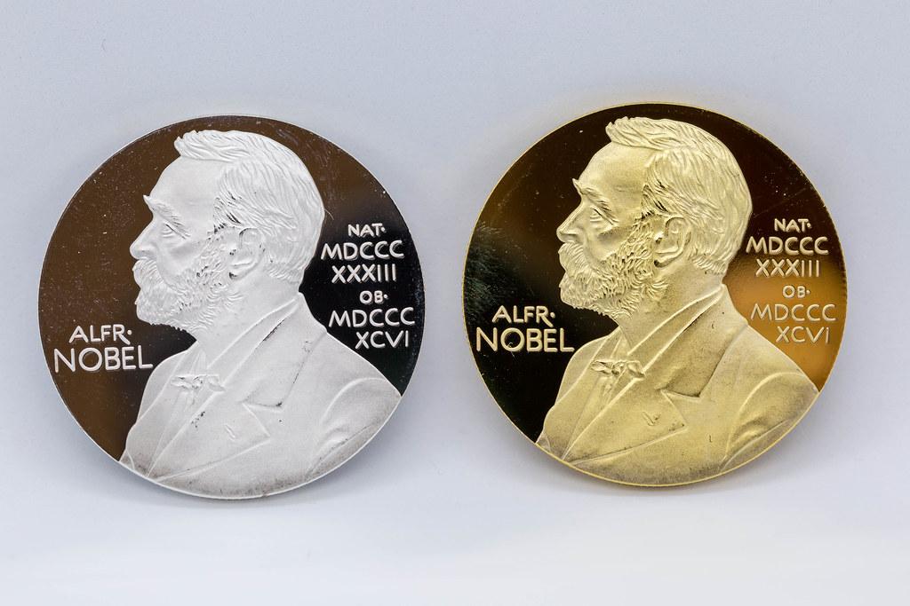 Makro-Fotografie: zwei Silber- und Goldmünzen mit dem Gesicht von Alfred Nobel