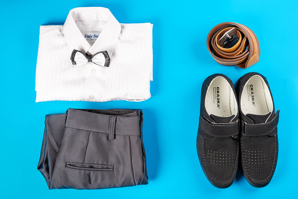 Male classic clothing on blue, top view - shirt, trousers, shoes and belt, top view