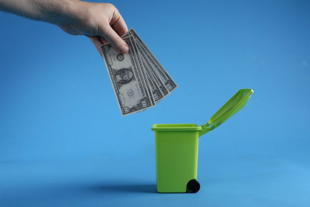 Male hand throwing bundle of money dollars into green trash bin on blue background