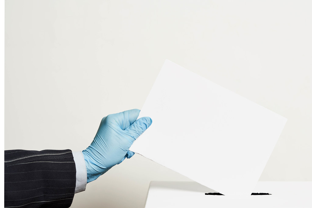 Male hand wearing blue protective latex glove placing ballot paper in vote box