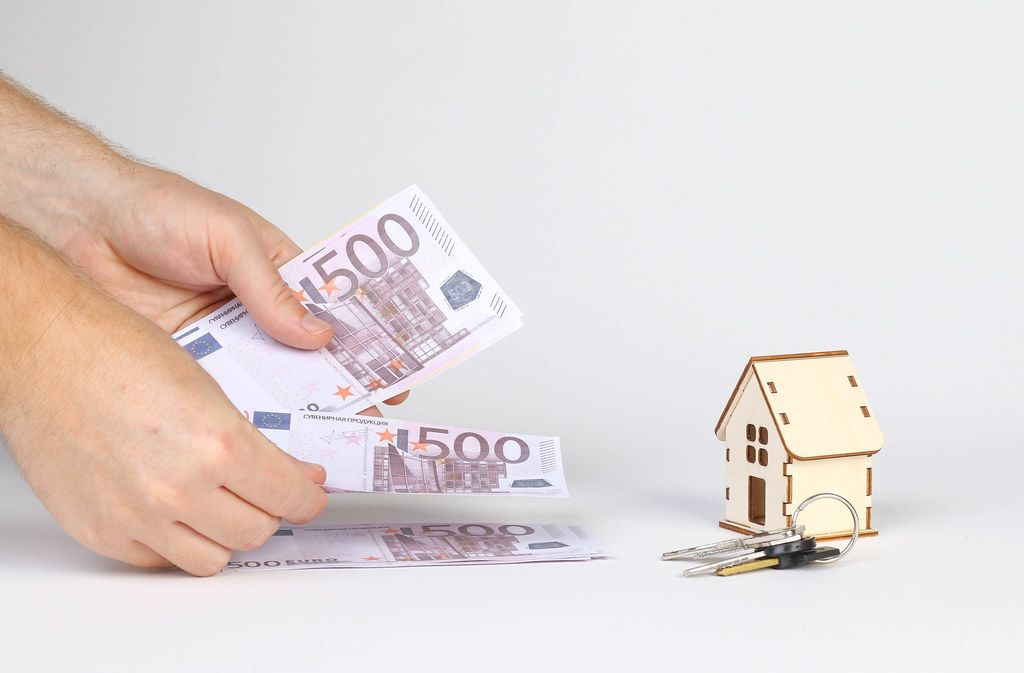 Man counting money with tiny wooden house and keys