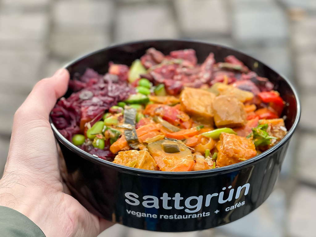 Man holding vegan food to go in the hand: black bowl by vegan restaurant