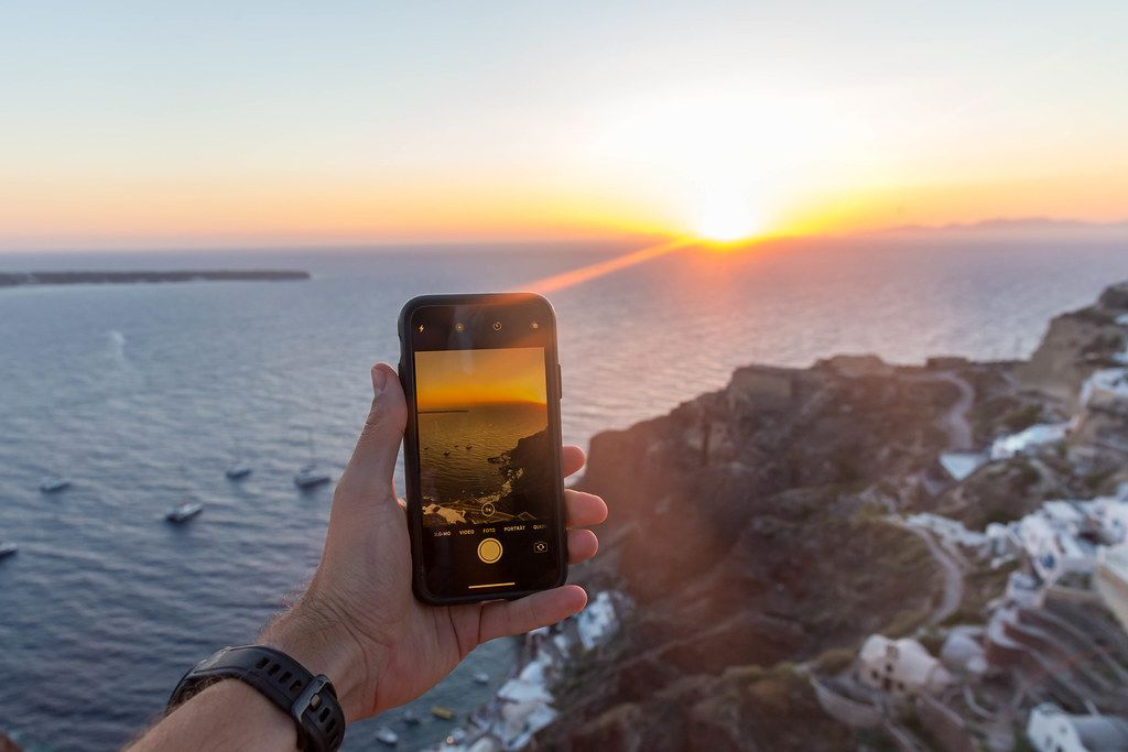 Man holds an iPhone in his hand while taking photos of the sunset in Oia, Santorini