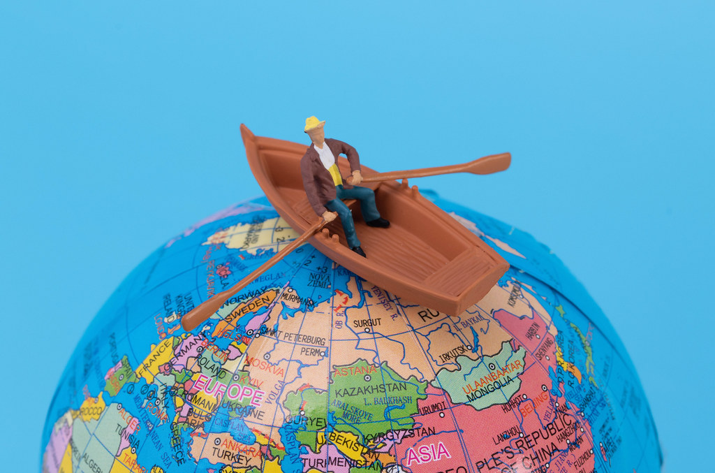 Man in a boat at top of the globe
