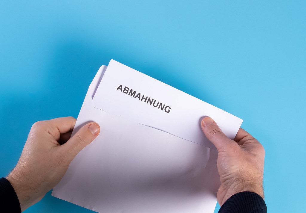 Man opening envelope with Abmahnung text
