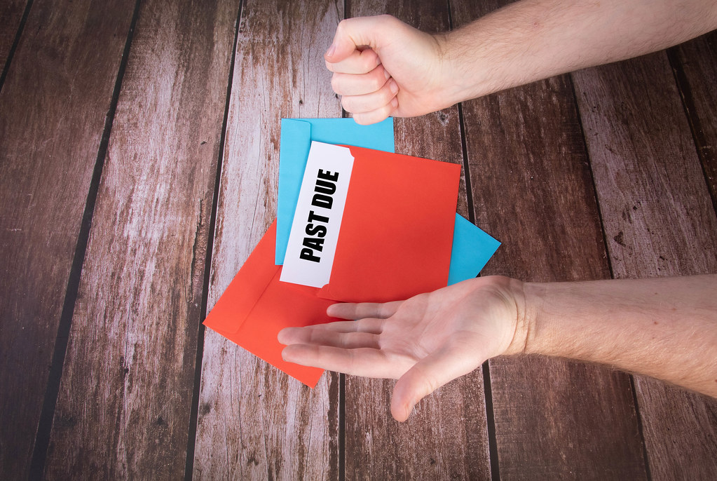 Man opens red envelope with Past Due text