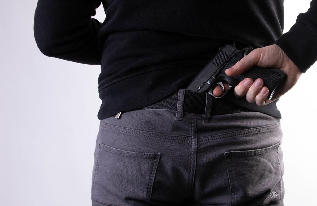 Man pulling gun from waistband