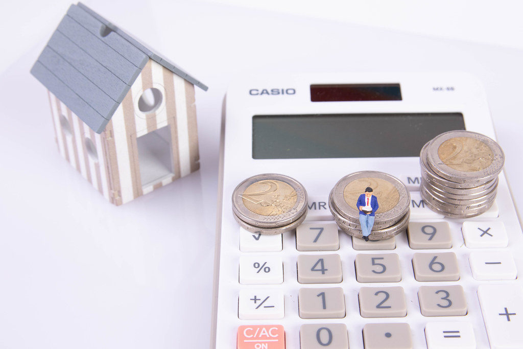 Man sitting on coin stack with calculator and small house