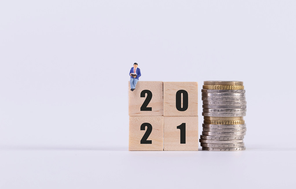 Man sitting on wooden cubes with 2021 text and stack of coins on white background