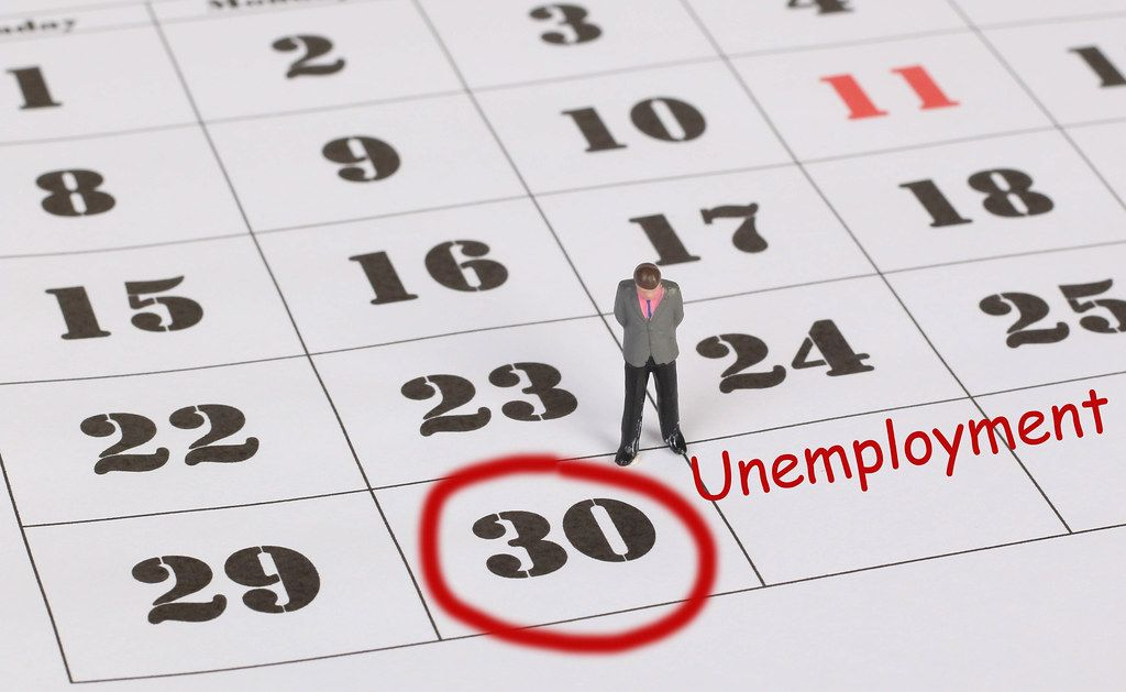 Man standing and looking at marked date with Unemployment text