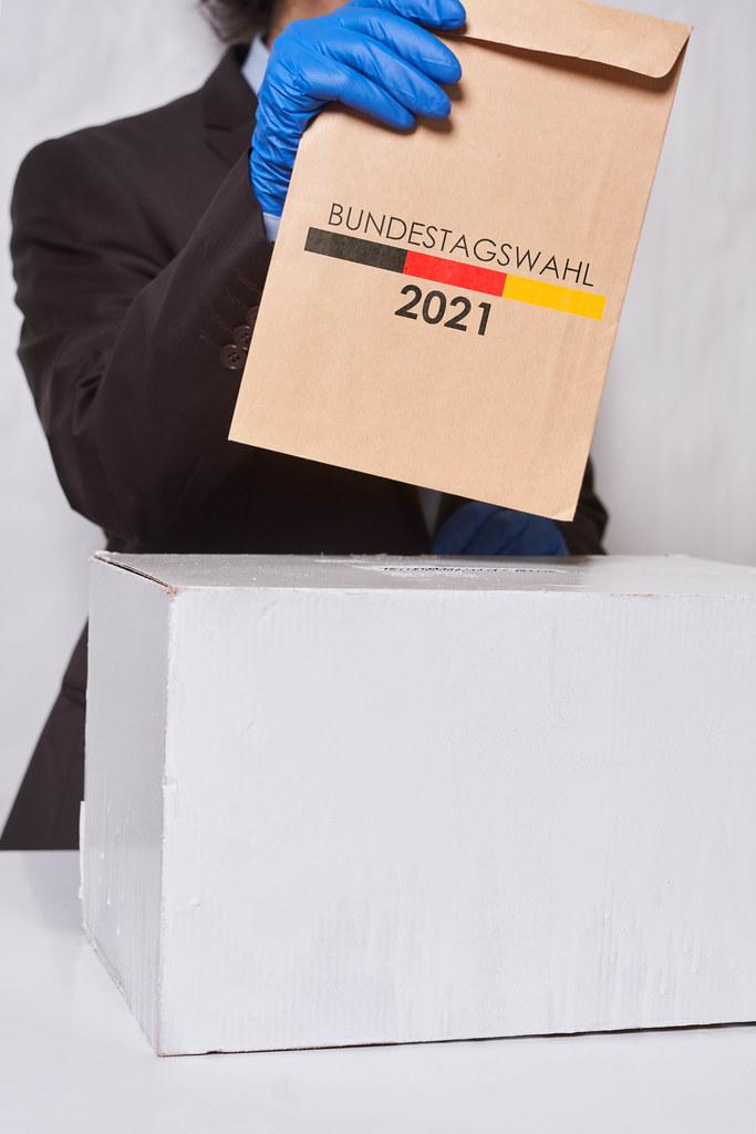 Man voter putting ballot into voting box - Bundestagswahl 2021